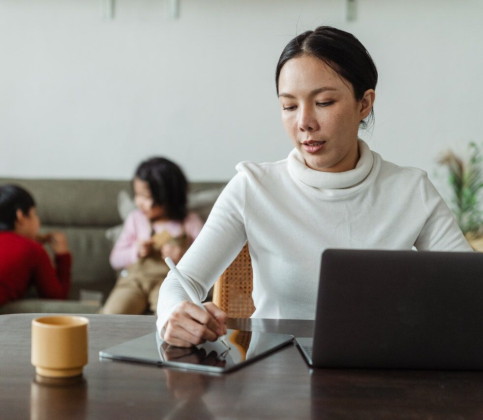 Young Woman working at home with children in background